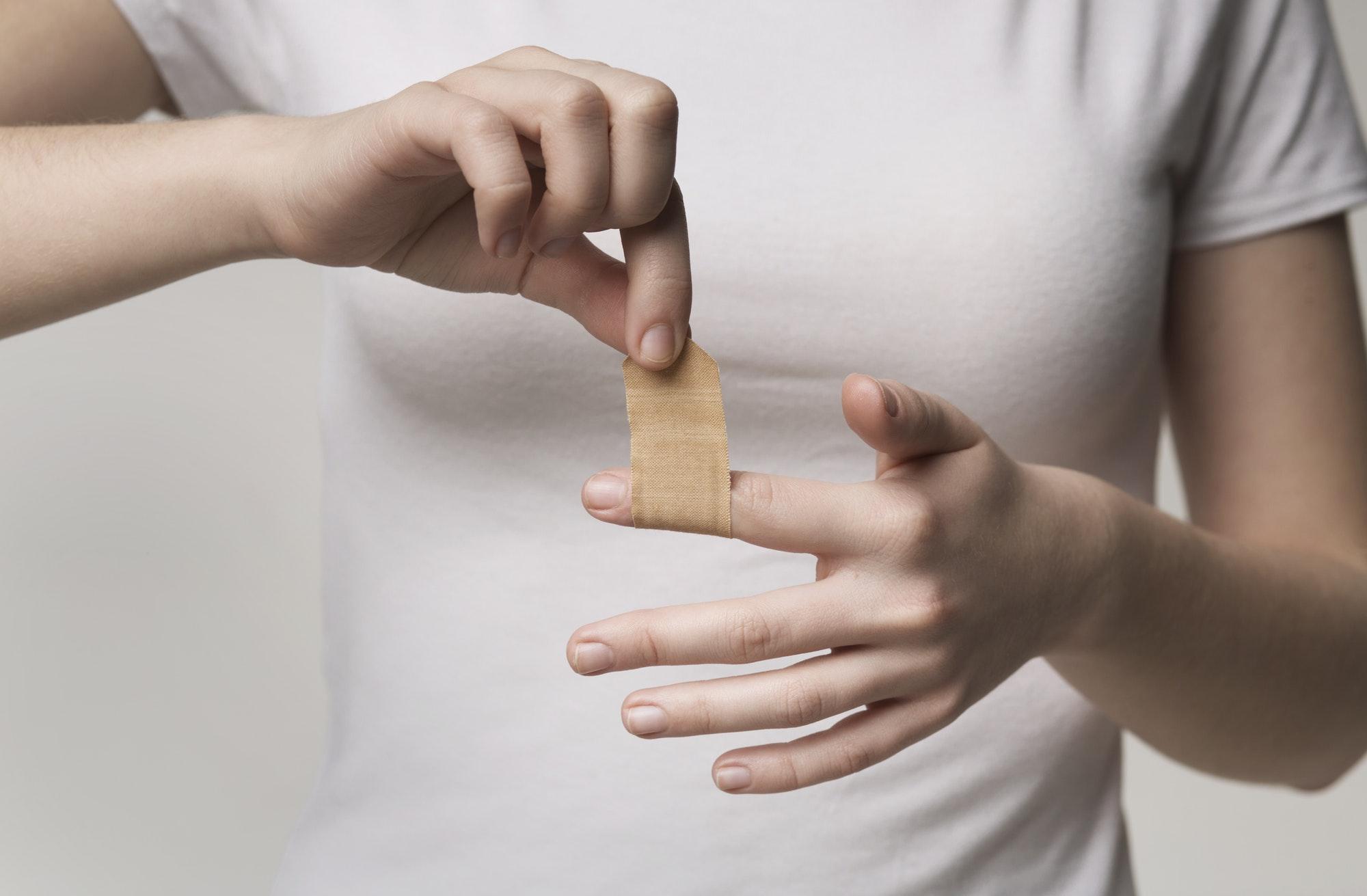 Woman using adhesive tape on injured finger