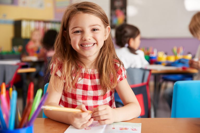 Portrait Of Smiling Female Elementary School Pupil Working At Desk