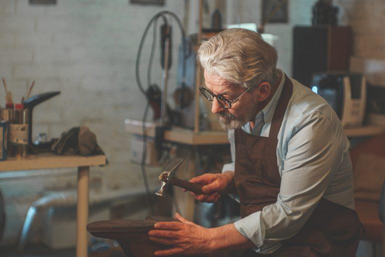 An elderly shoemaker at work indoors