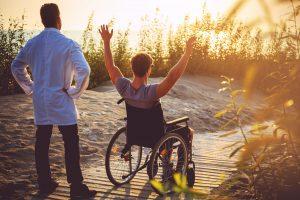 A man on wheelchair and his nurse.