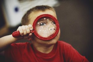 Little boy and magnifying glass