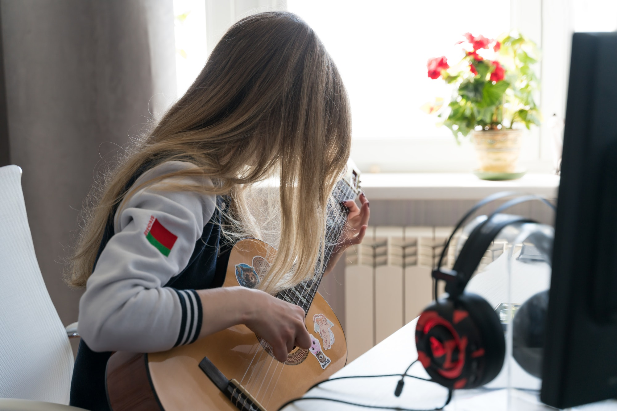 girl playing guitar in the room by the window