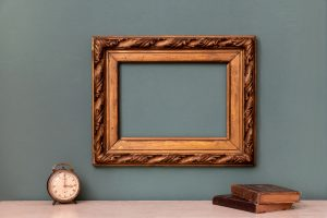 Empty gold vintage picture frame with books